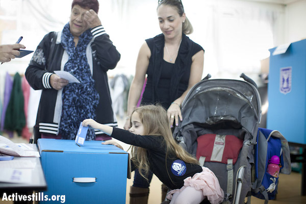 A small Israeli girl casts her mother's vote in the 2013 Knesset elections. (photo: Yotam Ronen / Activestills)