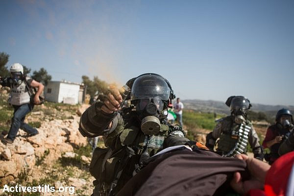 An Israeli border policeman uses pepper spray against a protester during a demonstration marking a decade of popular struggle against the wall in the West Bank village Bil'in, February 27, 2015. (photo: Yotam Ronen/Activestills.org)