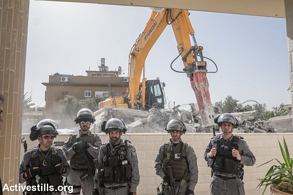 Israeli police officers stand guard as the home of Hana al-Nakib and her four children is demolished, in the city of Lod, February 10, 2015.  (Yotam Ronen/Activestills.org)