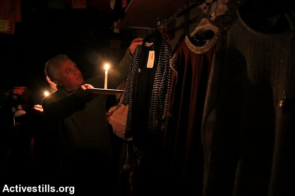 A vendor in Nablus uses a candle in his store, after Israel Electric Company deliberately shut down power to the city and the surrounding area. (photo: Ahmad al-Bazz/Activestills.org)