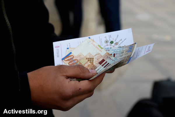 A Palestinian public-sector worker holds part of his salary withdrawn from an ATM, Nablus, West Bank, February 9, 2015. (photo: Ahmad Al-Bazz/Activestills.org)