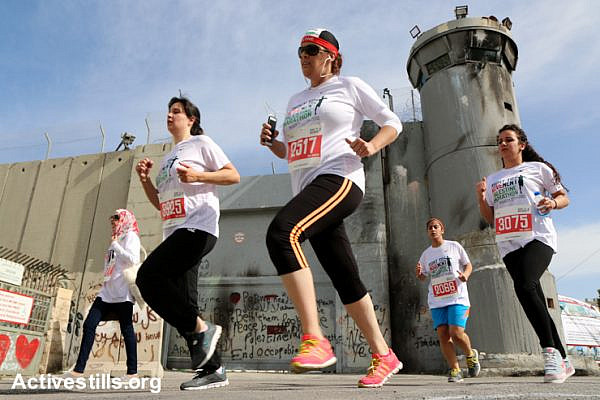 """Runners pass the Israeli Separation Wall dividing the West Bank city of Bethlehem in the third annual Palestine Marathon, March 27, 2015. Some 3,200 Palestinian and international runners participated in 10K, half marathon and full marathon races under the title """"Right to Movement"""". Full marathon runners had to complete two laps of the same route, as organizers were unable to find a single course of 42 uninterrupted kilometers under Palestinian Authority control in the area."""