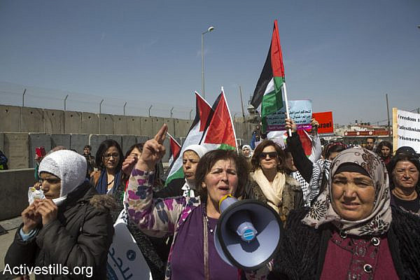 Palestinian women march toward the Qalandia checkpoint separating Ramallah and Jerusalem. Israeli soldiers broke up the joint Israeli-Palestinian protest against the occupation, a day before International Women's Day, March 7, 2015. (Anne Paq/Activestills.org)