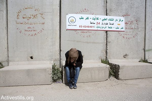 A Palestinian woman suffers from tear gas inhalation during a demonstration against the occupation held one day before International Women's Day, at Qalandia checkpoint, West Bank, March 7, 2015. (Anne Paq/Activestills.org)