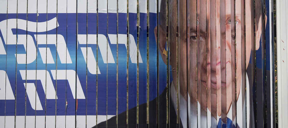 A campaign billboard for Netanyahu's Likud switches to a billboard for Isaac Herzog's Zionist Camp. (Oren Ziv/Activestills.org)