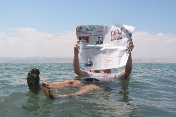 A man reads a newspaper while floating in the Dead Sea. (Author unknown, WikiCommons)