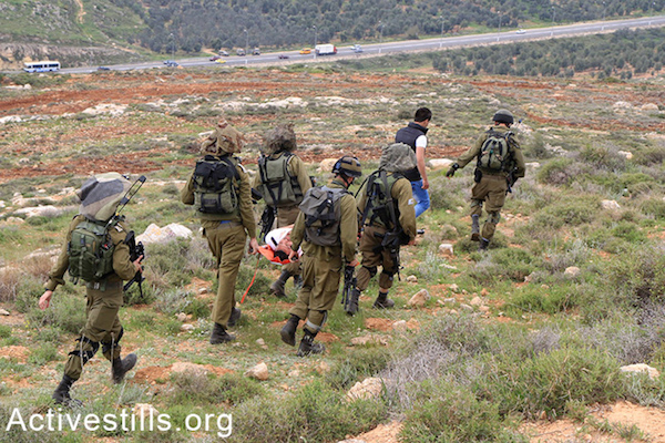 Israeli soldiers take away two Palestinians they've arrested, one of them while unconscious, Qaryut, West Bank, March 15, 2015. (photo: Activestills.org)