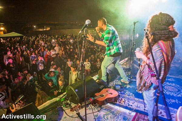 Rapper Tamer Nafar performs during a cultural event in the unrecognized village of Dahmash on March 14, 2015. (photo: Yotam Ronen/Activestills.org)