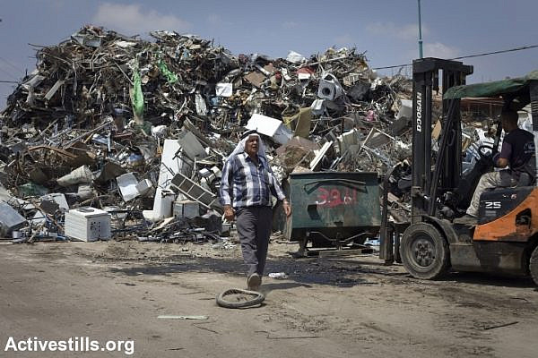 A resident works at a metal recycling compound, in the unrecognised village of Dahamash, Israel, July 22, 2010. (photo: Oren Ziv/Activestills.org)