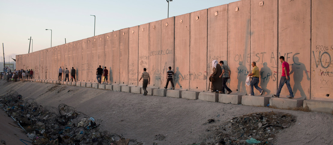 Palestinians walk along the separation wall in the West Bank. (Activestills.org)