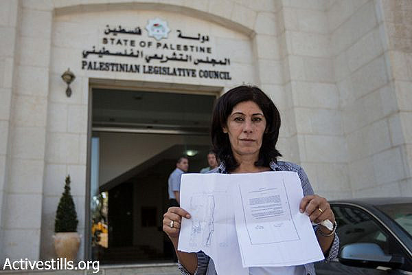 Khalida Jarrar, a member of the Palestinian Legislative Council and a leader in the Popular Front for the Liberation of Palestine, poses for a photo showing an internal expulsion order given to her by Israeli soldiers who invaded her home in Ramallah in the early hours of August 20, Ramallah, West Bank, August 27, 2014. Jarrar was ordered to go to Jericho within 24 hours, but she refused to sign the paper. She is determined to stay in a protest tent in front of the Palestinian Council in Ramallah until the decision is revoked.