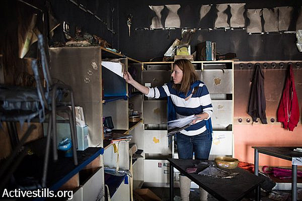 "A teacher inspects the damage in the aftermath of an arson attack that targeted first-grade classrooms at a bilingual Jewish-Arab school near the Palestinian neighbourhood of Beit Safafa, in southern Jerusalem, November 30, 2014. Anti-Arab slogans were scrawled on the walls in Hebrew reading: ""Death to Arabs"", and ""There's no coexistence with cancer."""