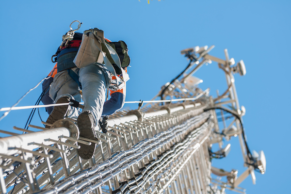 Stock photo of a worker climbing a cellular antenna tower. (Shutterstock.com)