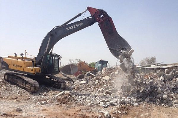 A bulldozer demolishes an apartment building in the unrecognized village Dahmash, April 15, 2015. (photo: Rami Younis)