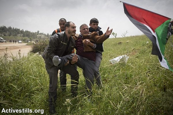 Protesters carry a Palestinian man who was injured during a protest marking Palestinian Prisoners' day, outside Ofer military prison, near the West Bank town of Betunia, April 16, 2015. (photo: Oren Ziv/Activestills.org)