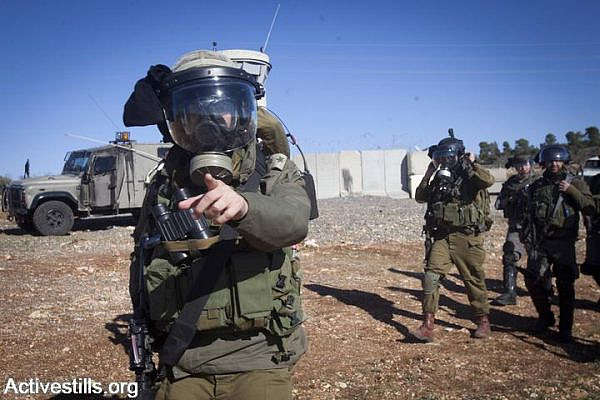 An Israeli soldier warns photographers during clashes following the funeral of Mustafa Tamimi in the West Bank village of Nabi Saleh, December 11, 2011. (photo: Oren Ziv/Activestills.org)