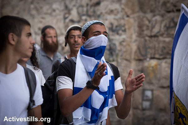 "An Israel youth covers his face with with a flag during the ""Jerusalem Day"" march held by Israeli nationalists to celebrate 48 years of the Israeli occupation of East Jerusalem, May 17, 2015."