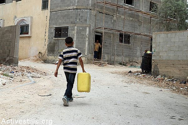 Palestinian child carries water gallon in Qarawat Bani Hassan village, West Bank, May 23, 2015. According to the municipal council of Qarawat Bani Hassan the portion of a each villager has decreased to two litters per day as the village receive only 97 Cubic meter per hour. The municipal council said the Israeli authorities did not provide the village with answers regarding the situation. Ahmad al-Bazz / Activestills.org