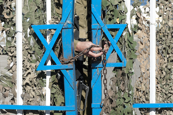 An Israeli soldier locks a border fence. (Illustrative photo by Shutterstock.com)