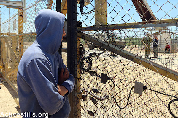 A Palestinian farmer stands beside an agricultural gate in the separation fence near Falamya village (Gate number 914), West Bank, May 17, 2015. Ahmad al-Bazz / Activestills.org