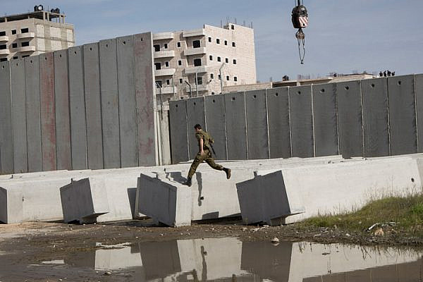 An Israeli soldiers is seen jumping along concrete blocks as Israeli authorities install a new section of the separation wall surrounding the Shuafat Refugee Camp in East Jerusalem, December 3, 2014. (Activestills.org)