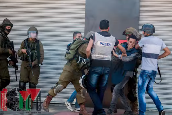 Soldiers assault journalists during clashes at Jalazone refugee camp in the West Bank. (photo by ISM)