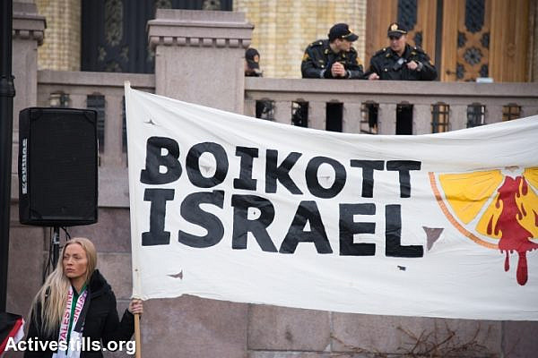 "Police watch from above as solidarity activists hold a banner reading ""Boycott Israel"" during a protest in front of the Norwegian Parliament building, Stortinget, Oslo, March 30, 2015. (photo: Ryan Rodrick Beiler/Activestills.org)"
