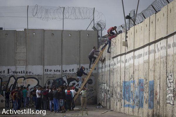 Dozens of Palestinians wait to climb over the separation wall near Qalandiya checkpoint, June 26, 2015. (photo: Oren Ziv/Activestills.org)