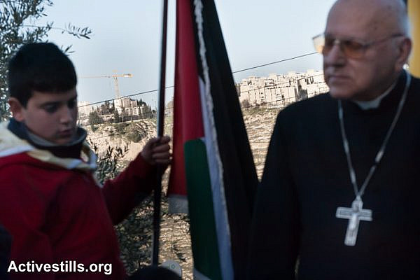 With the Israeli settlement Gilo visible on a nearby hillside, Latin Patriarch Emeritus Michel Sabbah joins Palestinians in a prayer service as a nonviolent witness against the Israeli separation barrier in the West Bank town of Beit Jala, February 8, 2013. All Israeli settlements are illegal under international law. (photo: Ryan Rodrick Beiler/Activestills.org)
