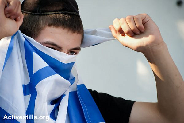 An Israeli settler youth living in a confiscated Palestinian home in the East Jerusalem neighborhood of Sheikh Jarrah covers his face with the Israeli flag, September 2, 2011. (photo: Ryan Rodrick Beiler/Activestills.org)