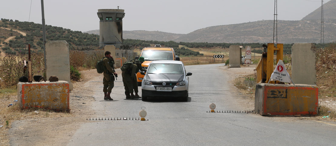 Israeli soldiers check cars at a checkpoint in the West Bank, May 27, 2015. (Activestills.org)
