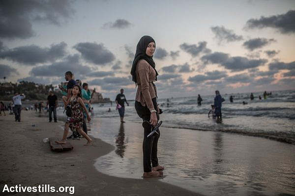 A Palestinian woman stands in the Mediterranean Sea during the last day of the Eid al-Fitr holiday as the sun sets in Tel Aviv, Israel, Sunday, July 19, 2015. Israeli authorities issued thousands of permits for Palestinians living in the West Bank, allowing them to visit Israel during the three-day holiday that marks the end of the holy fasting month of Ramadan. (photo: Yotam Ronen/Activestills.org)