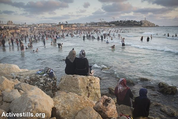 Palestinians, many of whom came from the West Bank, sit near the Mediterranean Sea during the last day of the Eid al-Fitr holiday as the sun sets in Jaffa, July 19, 2015.