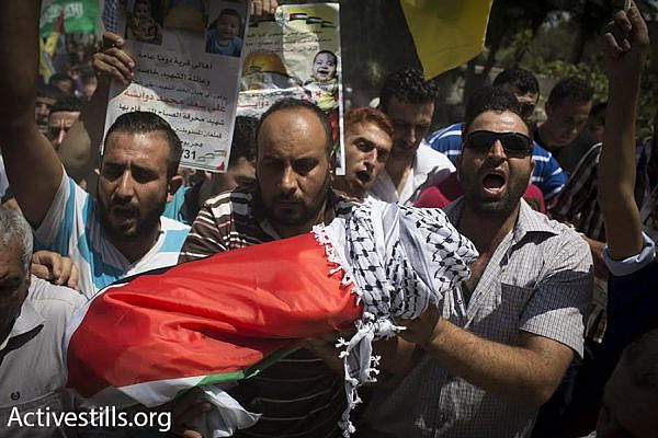 Palestinians in the West Bank village of Duma carry the body of 18-month-old Ali Saad Dawabshe after he was slain in an arson attack during the early hours of the morning, July 31, 2015. (Oren Ziv/Activestills.org)