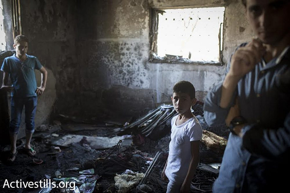 Palestinians gather at the Dawabsheh family home in the West Bank village of Duma following an arson attack by Jewish terrorists, August 1, 2015. (Oren Ziv/Activestills.org)