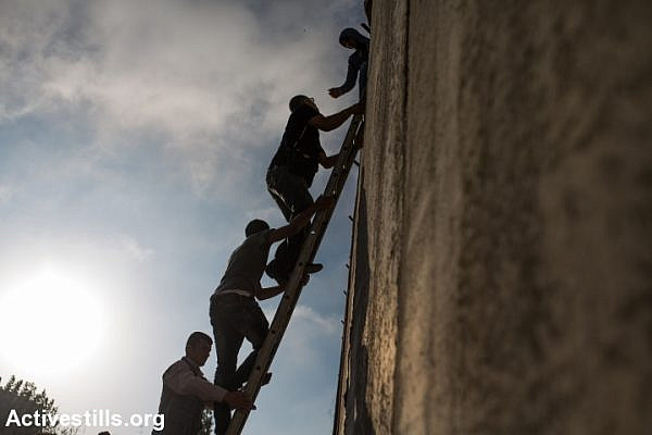 Palestinians climb over the Israeli Wall to attend the Friday prayer in Al-Aqsa Mosque, in the town of Al-Ram, near the Qalandiya checkpoint between the West Bank city of Ramallah and Jerusalem, on the second Friday of the Muslim holy month of Ramadan, July 3, 2015. (Yotam Ronen/Activestills.org)