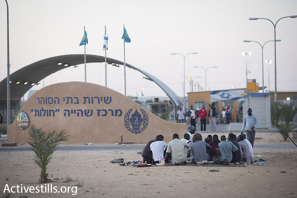 Sudanese asylum seekers sit in groups outside the gates of the Holot detention facility while they wait for the daily Ramadan fast to end, July 2015. (Oren Ziv/Activestills.org)