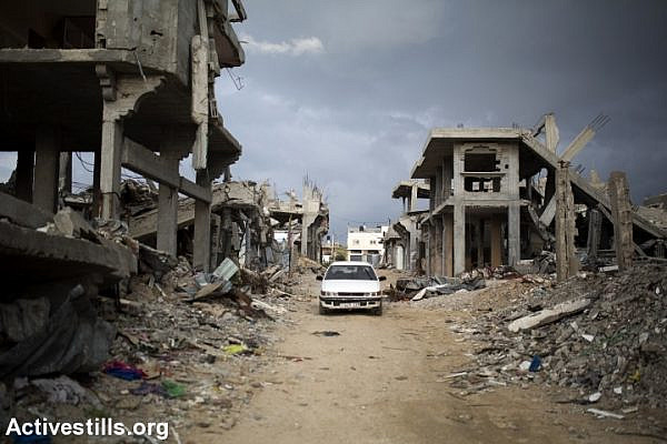 Palestinians drive through a destroyed quarter of Al Shaaf area in Al Tuffah, east of Gaza City, March 21, 2015. (Anne Paq/Activestills.org)