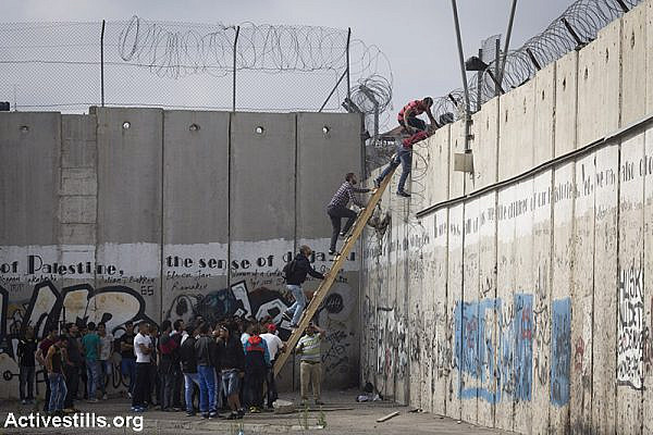 Palestinians climb over the Israeli Wall to attend the Friday prayer in Al-Aqsa Mosque, in the town of Al-Ram, near the Qalandiya checkpoint between the West Bank city of Ramallah and Jerusalem, on the second Friday of the Muslim holy month of Ramadan, June 26, 2015. (Activestills.org)