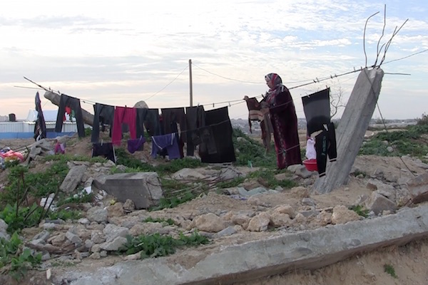 Hanging laundry from rubble in what was once the Awajah family home, destroyed during the 2014 war. (Photo by Jen Marlowe