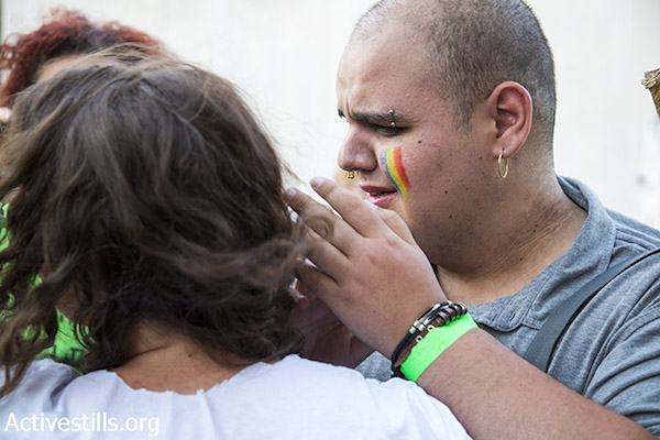 A man is seen crying following a mass stabbing attack against the Jerusalem LGBTQ Pride Parade in Jerusalem, July 30, 2015. (Keren Manor/Activestills.org)