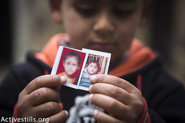 Fadi Ibrahim Abu Khusa (4) holds the photo of his two killed siblings, Shahed (9) and Mohammed (2), in their home in Zawaida village, central Gaza Strip, February 24, 2015.  The two children were killed with their parents, Ibrahim and Sabreen, and 4 other members of their family by an Israeli attack on their home which occured on July, 30, 2014. Ibrahim and Sabreen went to the home of Sabreen's father one week before the attack thinking they would be safer. (Anne Paq / Activestills.org)
