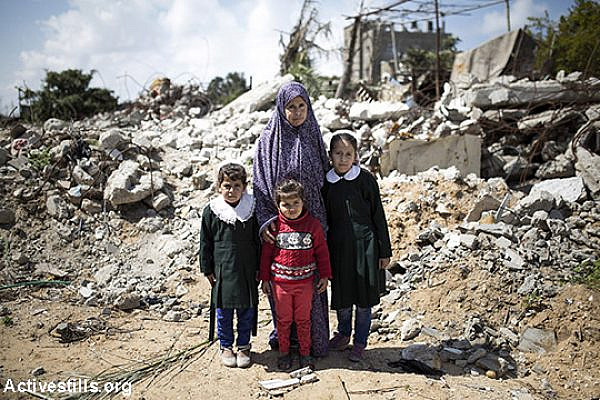 Elizabeth Tanboura stands with three of her daughters: Sundos, Malak, and Marwa (right), in front of their destroyed home in Beit Lahiya, Gaza Strip. Elizabth lost her husband and 2 of her children during an Israeli attack on August 25, 2014. Two other boys survived as they were not in the house at the time of the attack. Photo taken March 19, 2015.  (Anne Paq/Activestills.org)