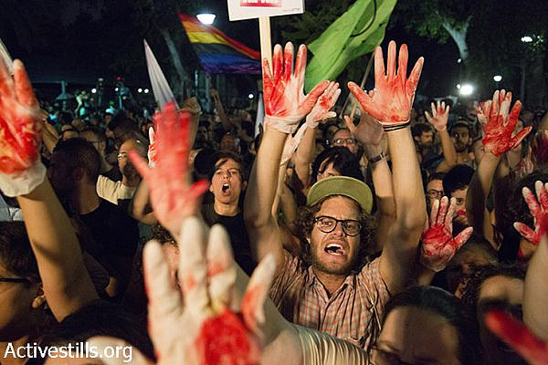 Israeli protesters wave red-painted hands and calling against racist and homophobic propaganda disseminated by Israeli government officials and members of Knesset during their speeches in protest against racism and homophobia, Tel Aviv, Israel, August 1, 2015. Protests were held tonight in Tel Aviv, Jerusalem, Haifa, Beer Sheva and Gan Shmuel Junction, following recent deadly attacks on the Dawabsha family and the stabbing attack in annual Jerusalem Pride Parade. (Activestills.org)