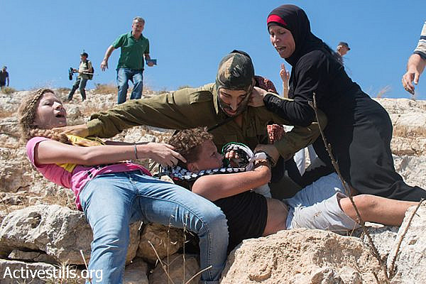 Members of the Tamimi family prevent from an Israeli solider from arresting Mohammed Tamimi, 11, during the weekly protest against the occupation in the West Bank village of Nabi Saleh, August 28, 2015. (photo: Muhannad Saleem / Activestills.org)