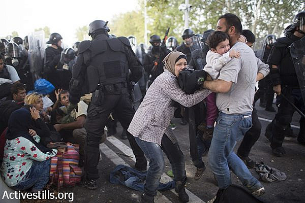 Hungarian policemen attack refugees during a protest in front a closed gate on the Serbian side of the Serbian-Hungarian border, September 16, 2015.