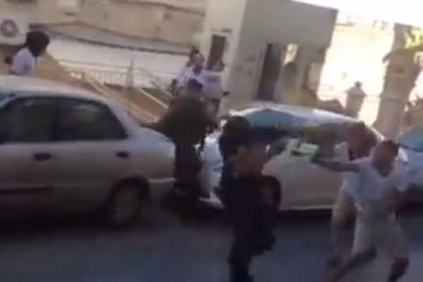 Screenshot of masked Israeli soldiers pepper spraying Palestinians detained at the Beit Hadassah checkpoint. (Courtesy of Youth Against Settlements)