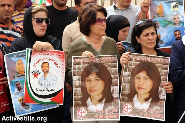 Women hold posters depicting imprisoned Palestinian parliamentarian Khalida Jarrar at a protest against administrative detention in Nablus. Jarrar was put under administrative detention before Israel finally indicted her under international pressure, Nablus, West Bank. September 10, 2015. (Ahmad Al-Bazz/Activestills.org)