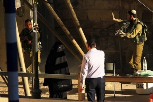 Bystander Fawaz Abu Aisheh attempts to translate the soldiers' commands for Hashlamon, and convinces her to step back behind the metal barrier. (Photo courtesy of Youth Against Settlements)