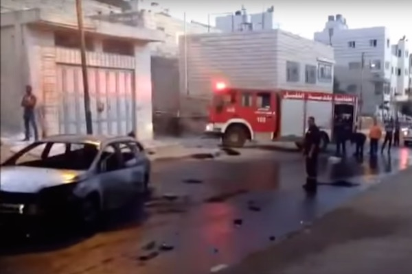 The burned-out car of five American yeshiva students who were attacked in Hebron by Palestinian youths. (Screenshot)